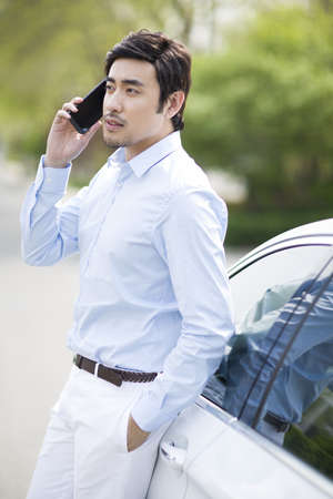 mode: Young man leaning on car and talking on the phone