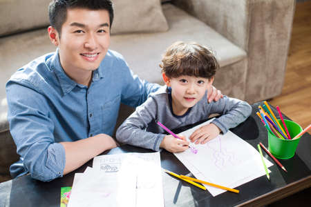 family: Young father helping son with homework