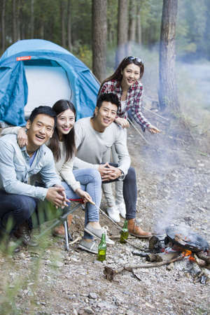 Young Chinese friends sitting beside campfire preparing food LANG_EVOIMAGES
