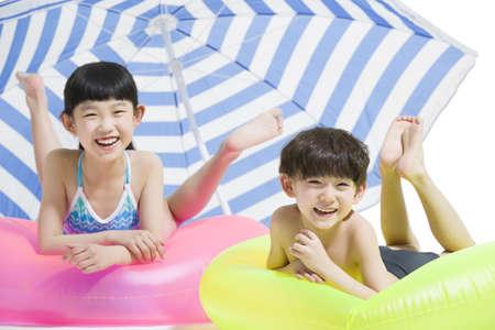 niño sin camisa: Cute niños en traje de baño con anillos de natación LANG_EVOIMAGES