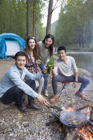 close range: Young Chinese friends sitting around campfire drinking beer LANG_EVOIMAGES