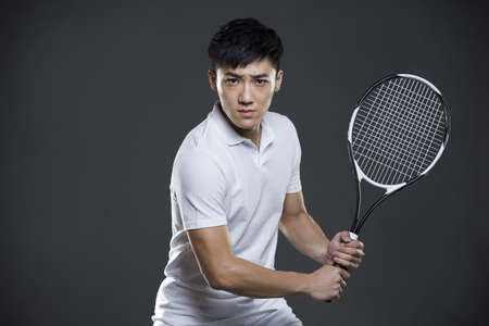 self conscious: Young man playing tennis LANG_EVOIMAGES