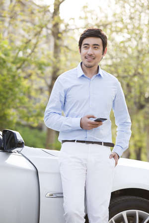 Young man leaning on car with smart phone LANG_EVOIMAGES