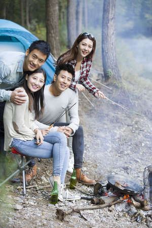 looking away from camera: Young Chinese friends sitting beside campfire preparing food LANG_EVOIMAGES
