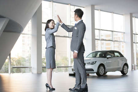 salespeople: Car salespeople high fiving LANG_EVOIMAGES