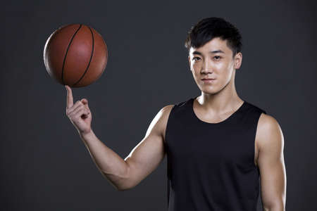 self conscious: Young man spinning basketball on finger