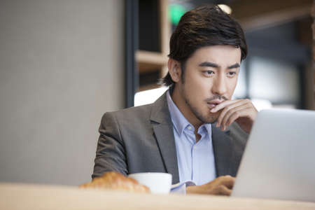 business: Chinese businessman working with laptop