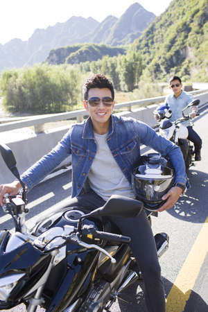 close range: Young Chinese friends riding motorcycle together