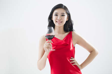 Elegant young woman enjoying red wine