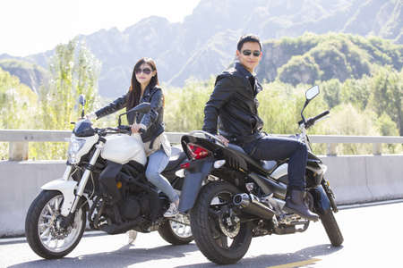 looking away from camera: Young Chinese couple riding motorcycle together