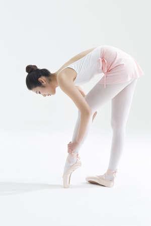 Ballet dancer tying up pointe shoes LANG_EVOIMAGES