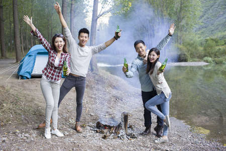 looking away from camera: Young Chinese friends standing around campfire drinking beer