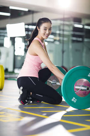 self care: Young woman lifting barbell at gym