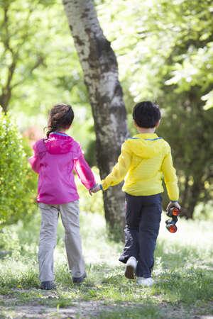 Happy children holding hands walking in woods LANG_EVOIMAGES