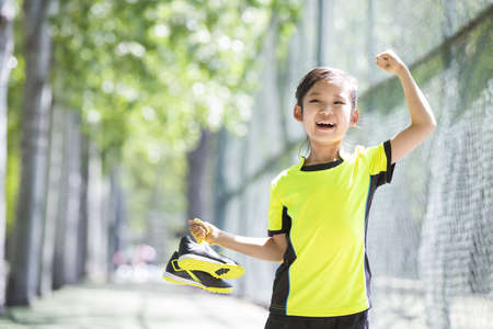 chainlink fence: Happy girl in sportswear cheering