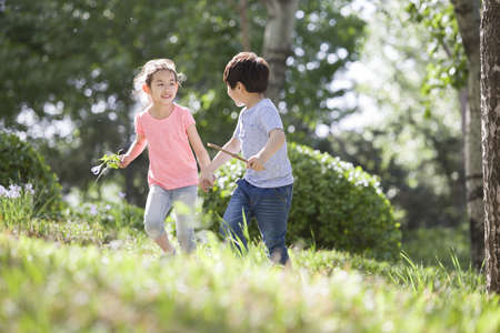 Happy children holding hands running in woods LANG_EVOIMAGES