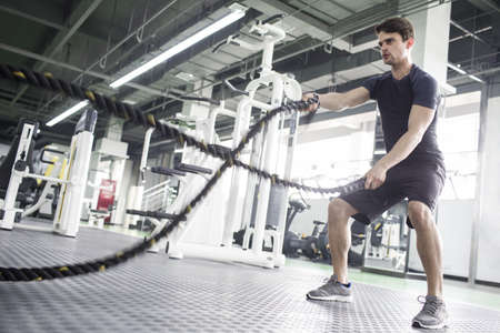 battling: Young man exercising with battling rope at gym LANG_EVOIMAGES