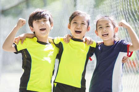 chainlink fence: Happy children in sportswear cheering LANG_EVOIMAGES