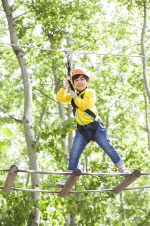 iluminado a contraluz: Niño pequeño jugando en el parque de aventura top árbol