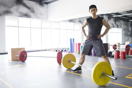 Young man exercising at gym LANG_EVOIMAGES