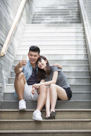 staircases: Young couple taking self portrait with smart phone