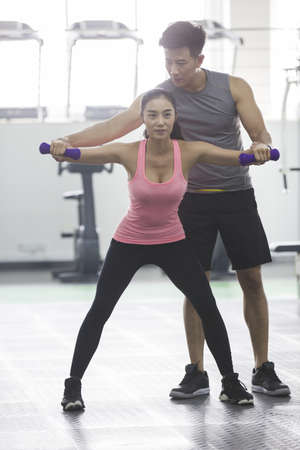 self care: Young woman working with trainer at gym