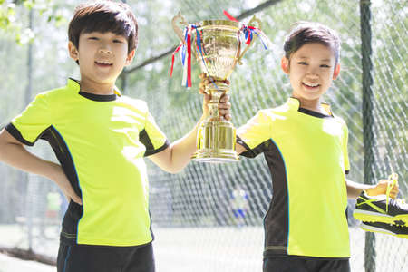 chainlink fence: Happy children in sportswear showing their trophy LANG_EVOIMAGES