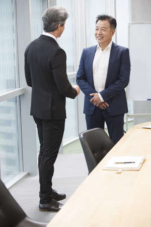 working attire: Businessmen talking in meeting room LANG_EVOIMAGES