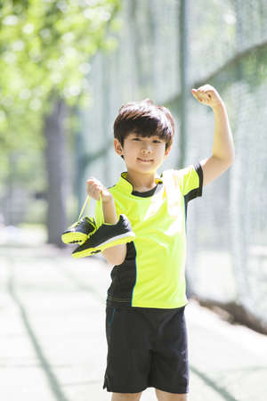 chainlink fence: Happy boy in sportswear cheering LANG_EVOIMAGES