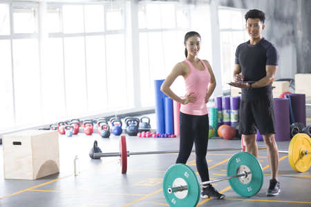 adult  body writing: Young woman working with trainer at gym