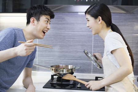 gas stove: Happy young couple cooking in kitchen