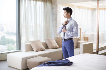 Young businessman getting dressed in the morning
