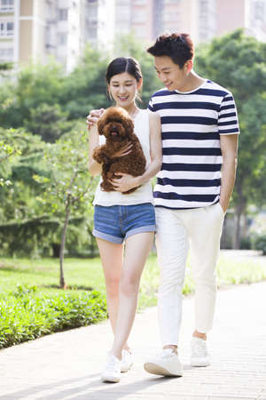 Young couple walking with a cute dog