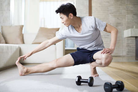 self care: Young man exercising at home