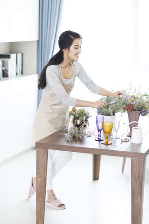 dried flower arrangement: Young woman arranging flowers at home