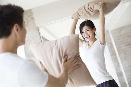 Young couple pillow fighting at home