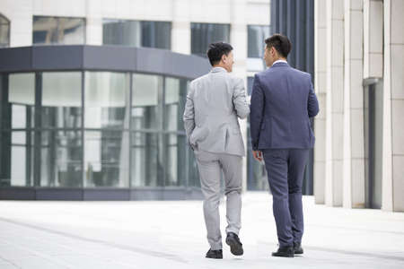 walking zone: Confident businessmen talking and walking outdoors