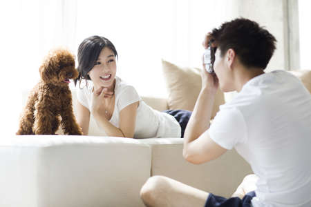 looking away from camera: Young couple taking photos at home