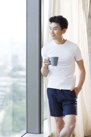 Young man drinking coffee at home LANG_EVOIMAGES