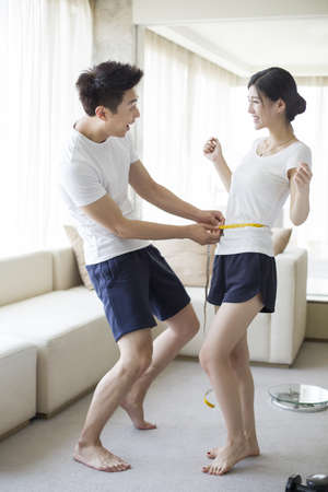 Young man measuring the waist of his wife LANG_EVOIMAGES