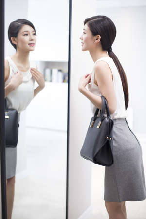 Young woman examining herself in front of mirror