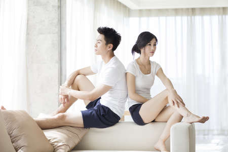 short shorts: Angry couple sitting on living room sofa