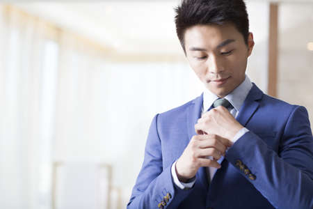 executive apartment: Young businessman getting dressed in the morning