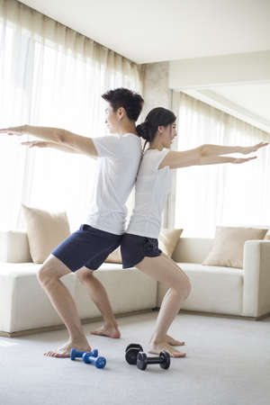 couple on couch: Young couple exercising at home