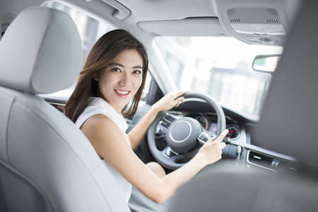 drivers seat: Confident businesswoman driving car