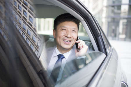 mode: Confident businessman talking on cell phone inside car LANG_EVOIMAGES