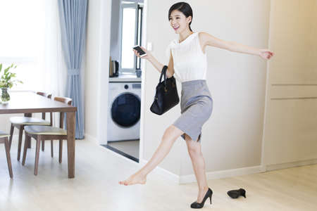 executive apartment: Young woman taking off her high heels after work LANG_EVOIMAGES