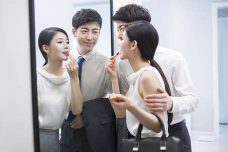 executive apartment: Young couple looking into a mirror before going to work LANG_EVOIMAGES