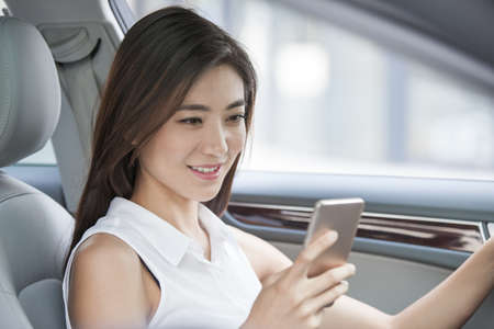 drivers seat: Confident businesswoman holding smart phone in a car