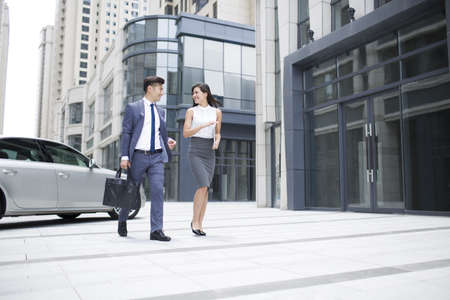 walking zone: Confident business people talking and walking outdoors LANG_EVOIMAGES